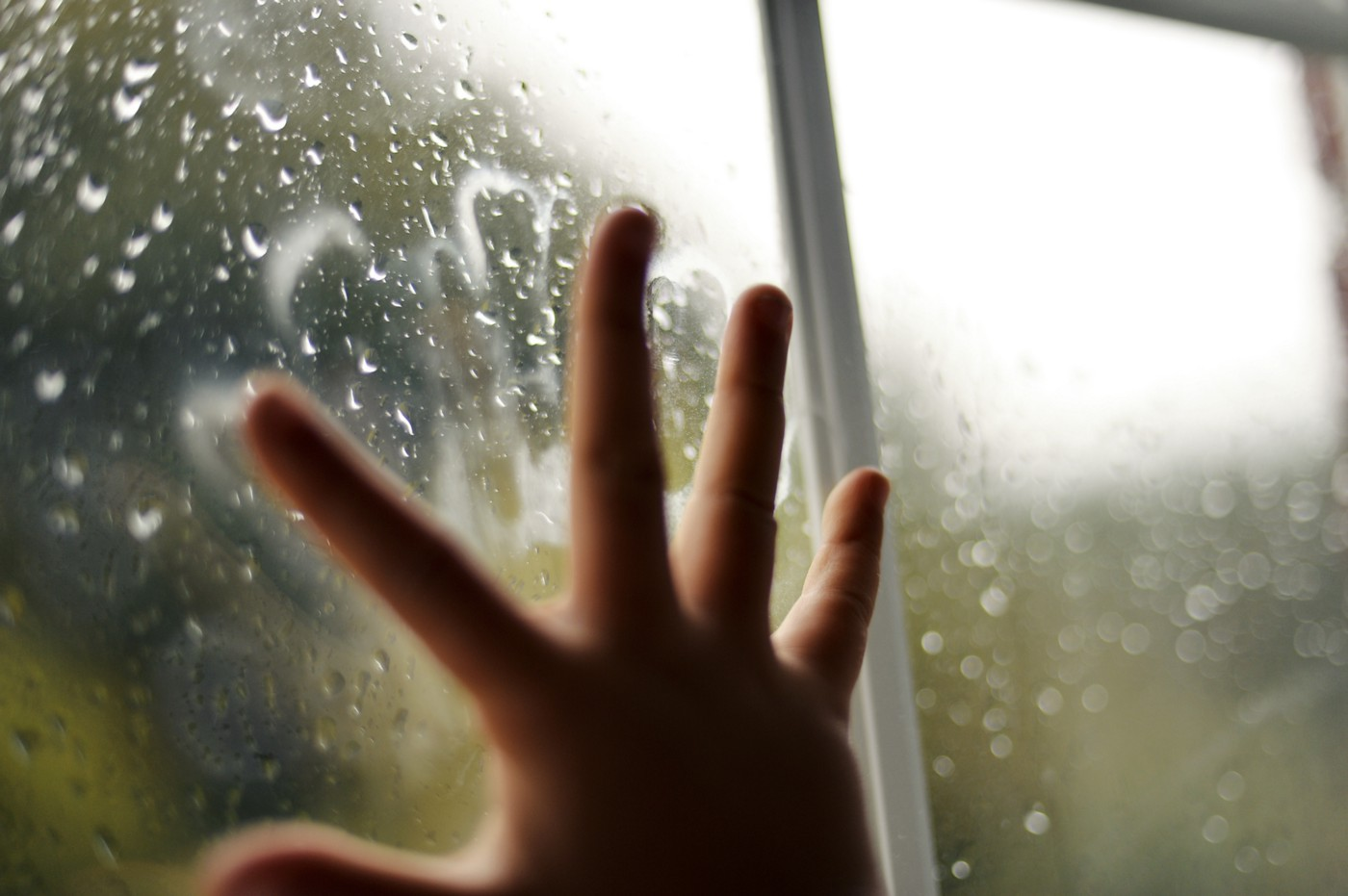 Childs hand pressed against window in home quarantine lockdown with rain drops and green leaves outside.