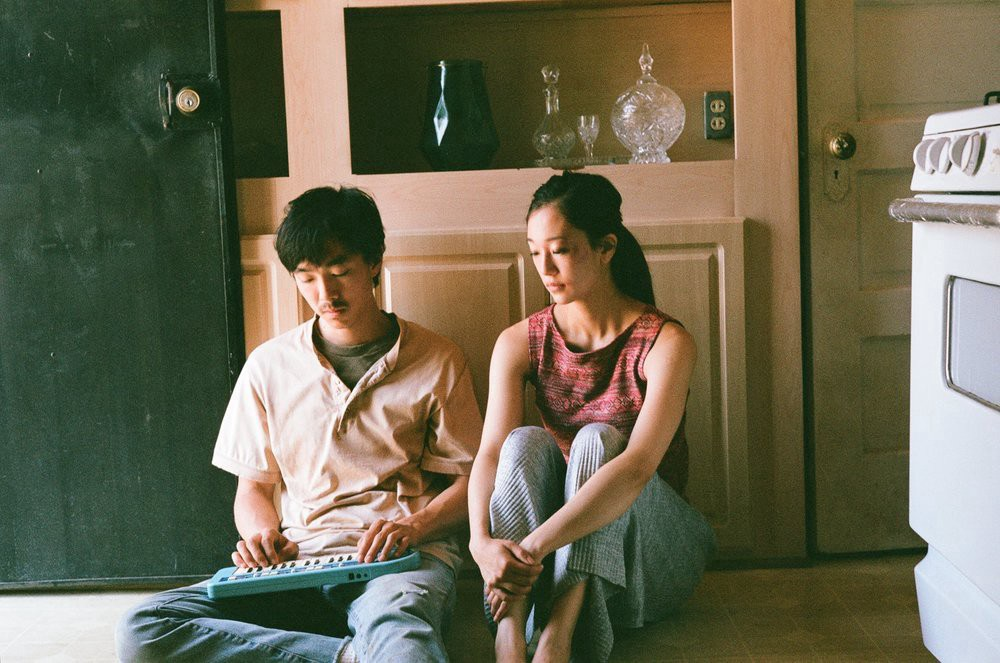 Teddy Lee (left) and Tiffany Chu (right), solemnly sitting on the floor of a kitchen, with Lee holding a toy piano.