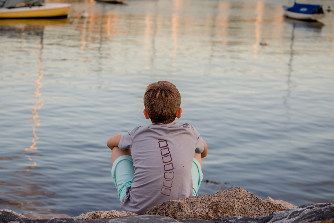 Young boy with scoliosis, sitting by the water.