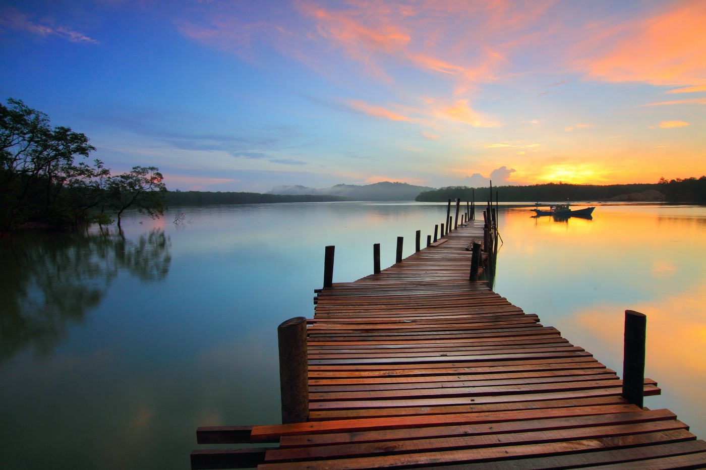 Wooden jetty leading out to lake with boat in distance at sunrise.