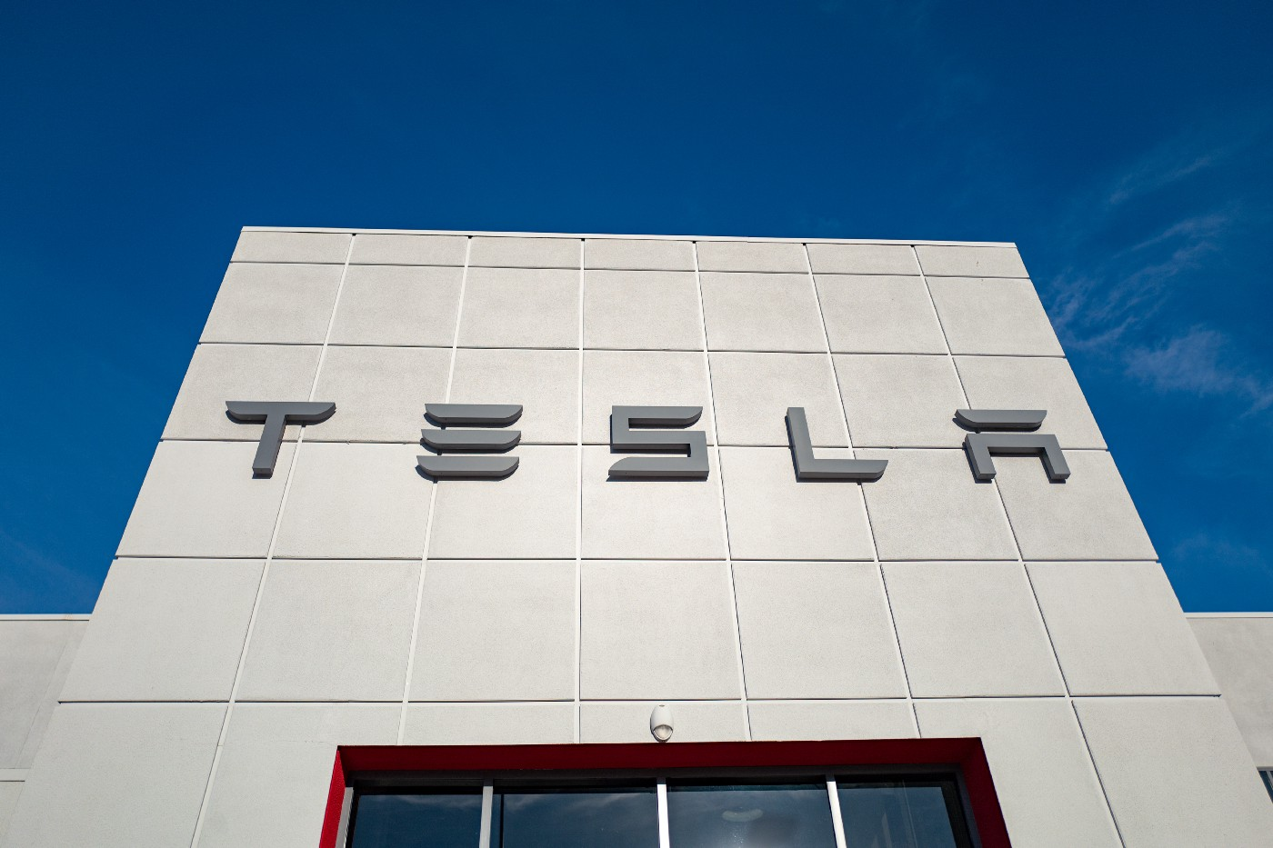 Low-angle view of the facade of Tesla Motors dealership with logo and sign in Pleasanton, California.