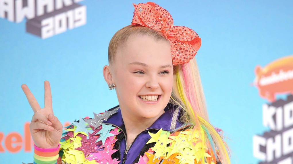 Jojo Siwa poses with a peace sign, wearing a big red bow and an outfit made of stars