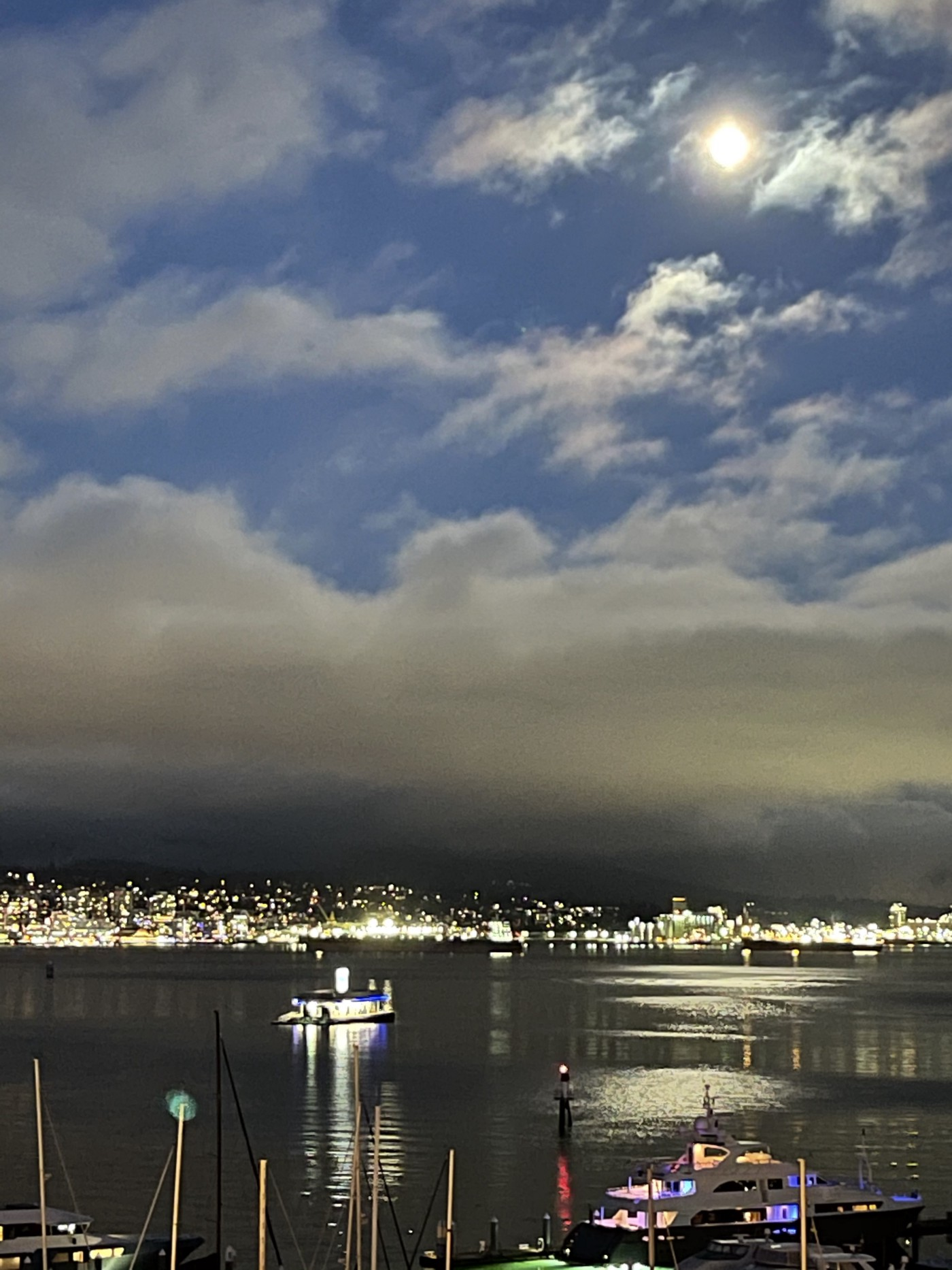 Blue dusk with almost full moon above low clouds, city and boat lights. The moon is reflected zigzagging on the water.