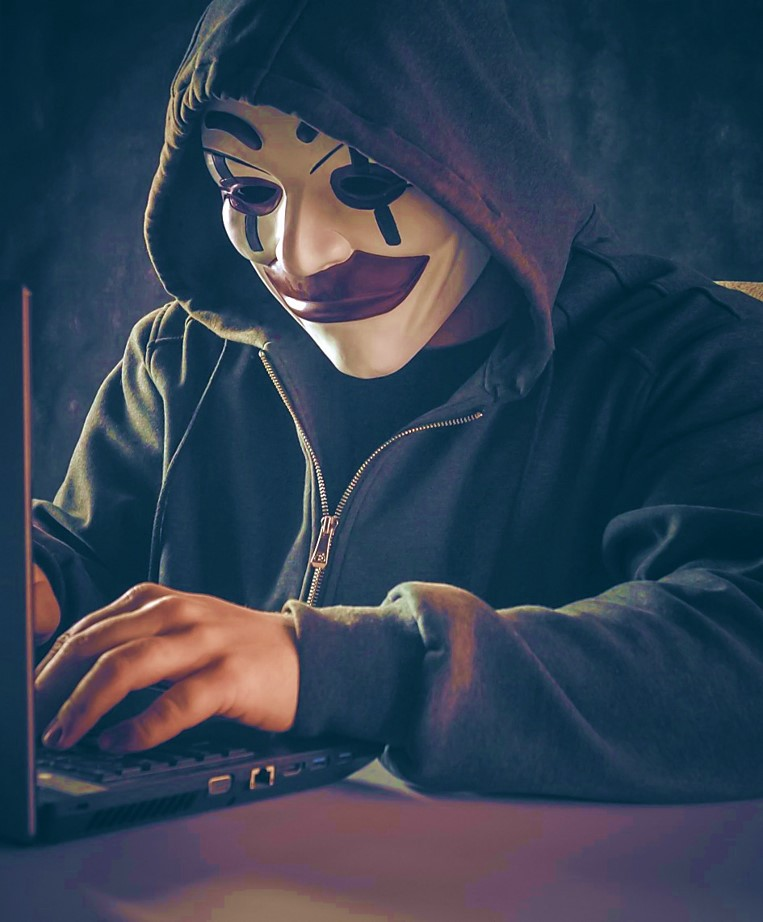 Hacker with a hoodie and evil clown mask typing on a laptop