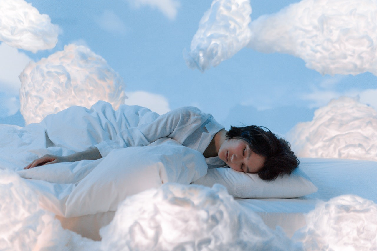 woman asleep, her bed drifting in the sky surrounded by puffy, white clouds