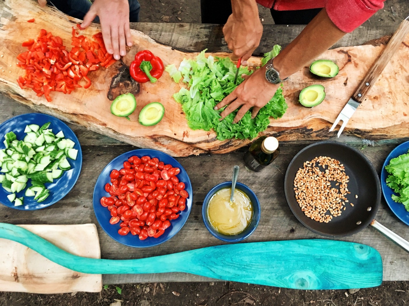 Two people preparing a meal with bright colored fresh vegetables