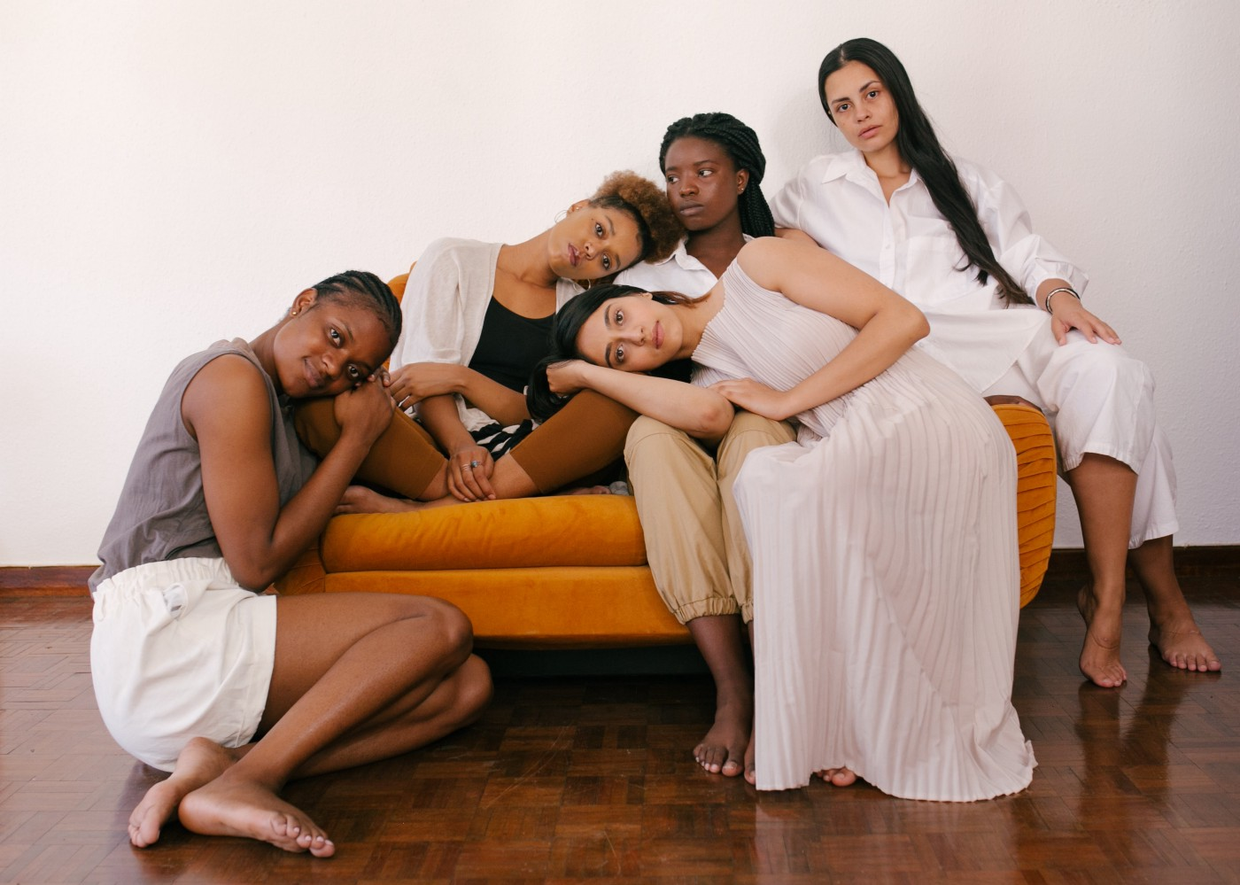 Five multiethnic women lounging on a couch