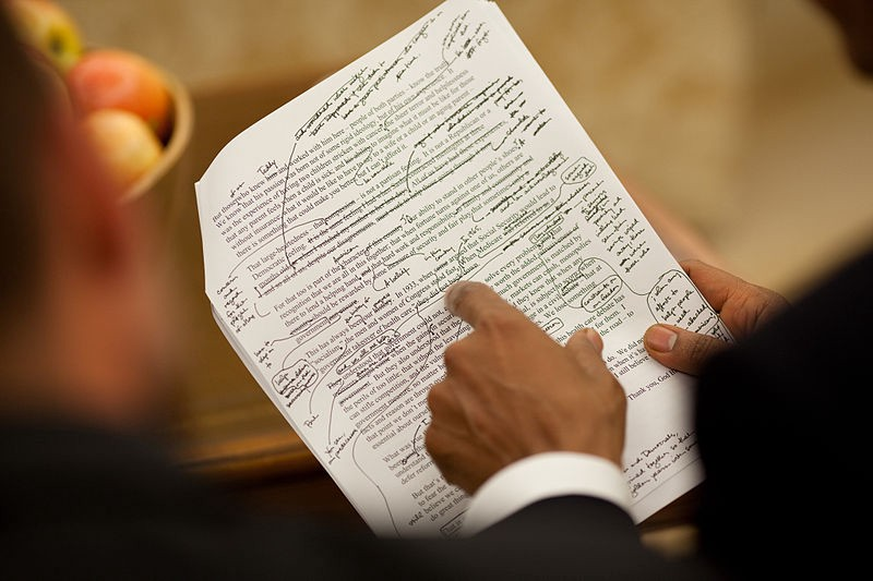 A picture of President Obama reviewing his handwritten edits to a printed draft of a speech.