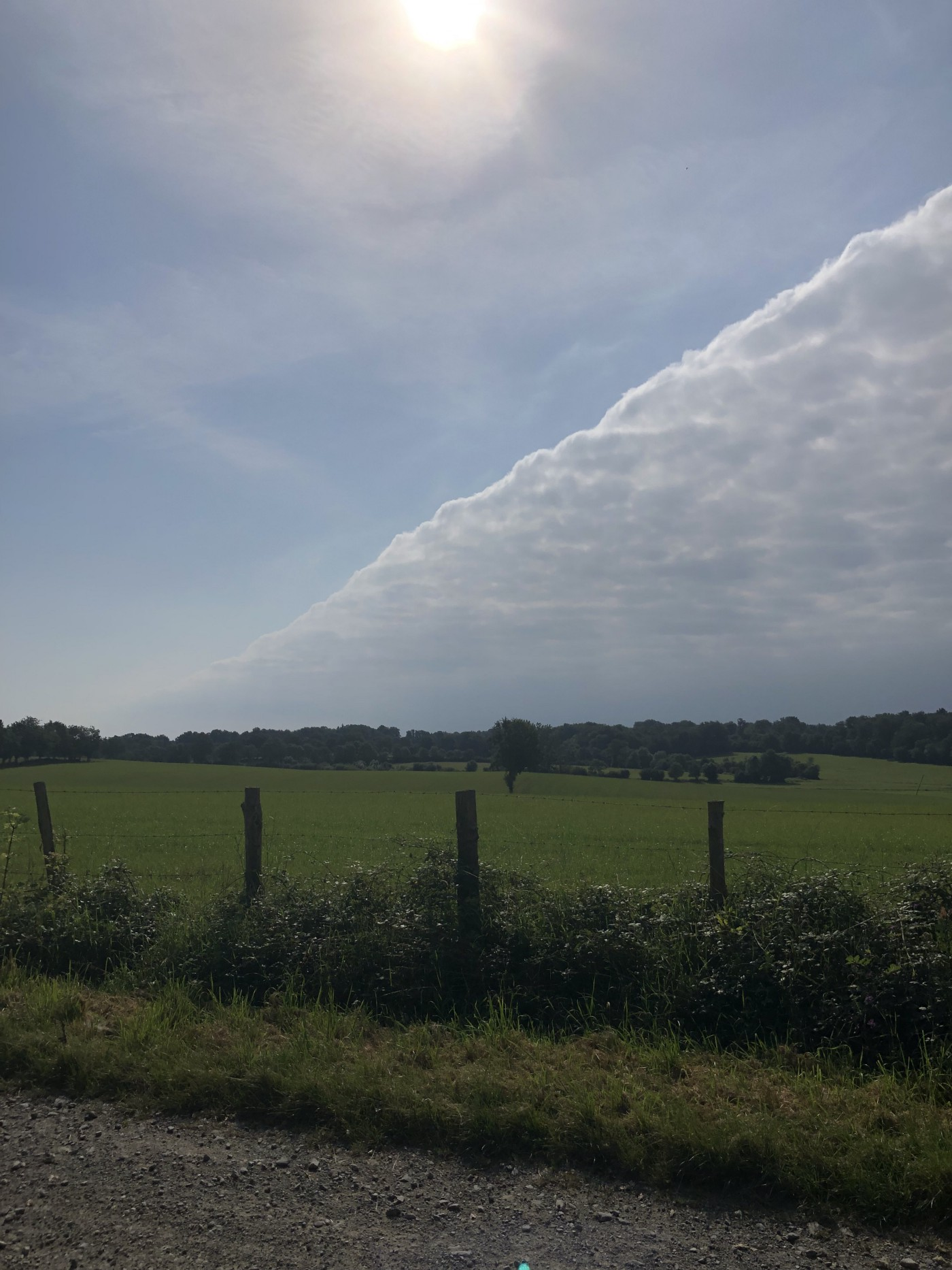 a stripe of clouds across the sky over a field, with a fence in the forwgrouind