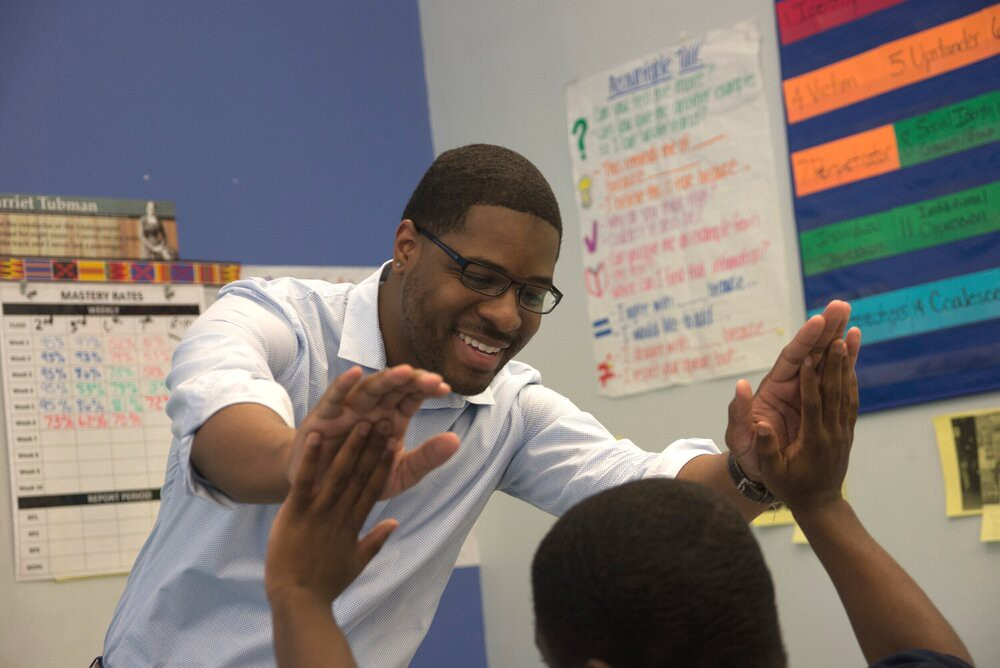 A teacher in a white shirt giving a student a double high five