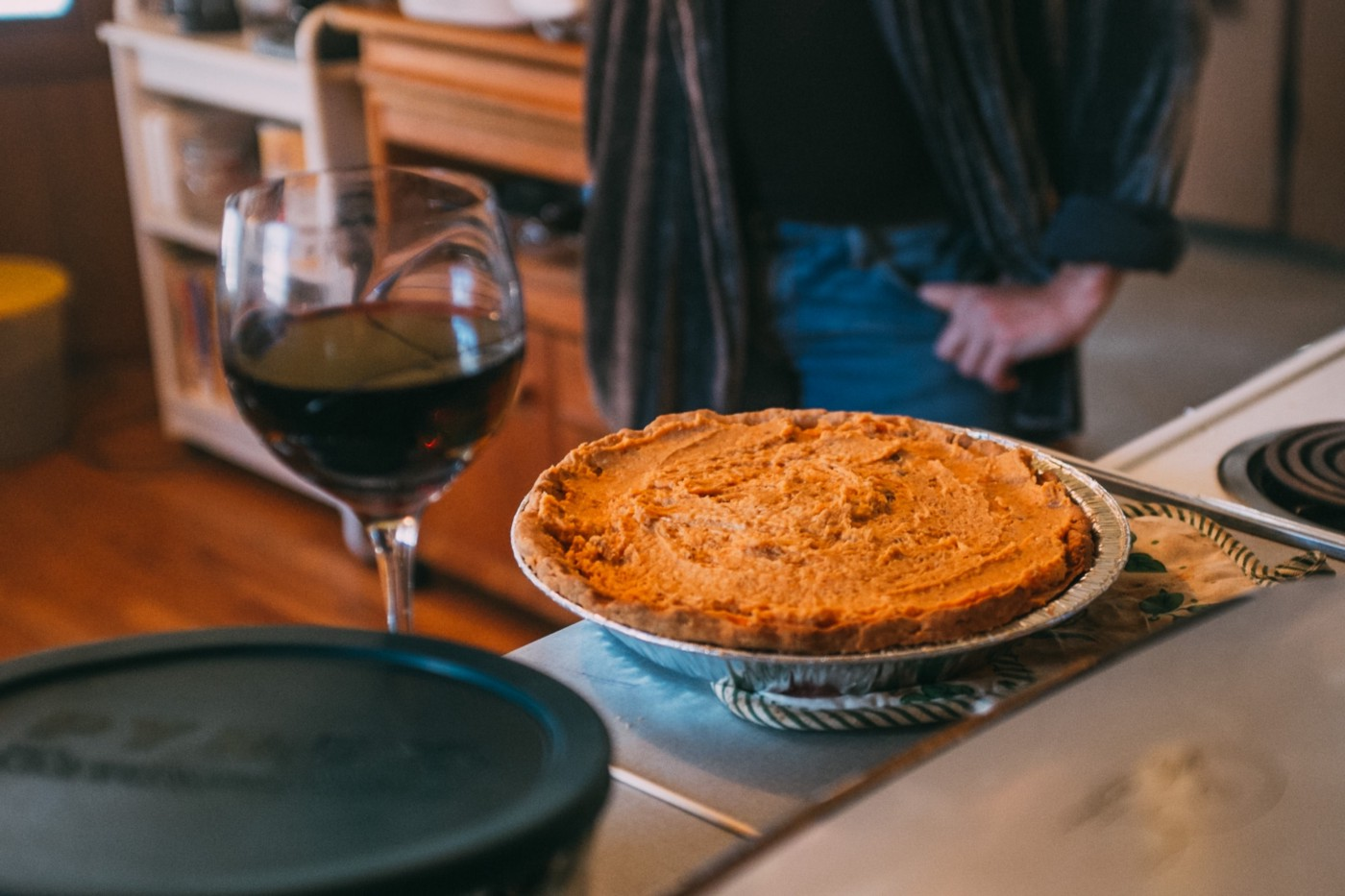 Person standing by a pumpkin pie and glass of red wine.