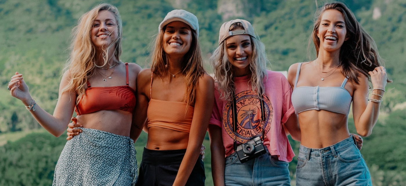 Four young women smiling and posing in front of a lush green mountain