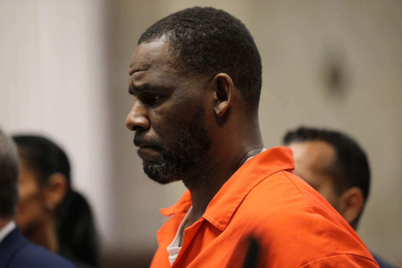 R. Kelly standing at a status hearing, wearing an orange prison jumpsuit