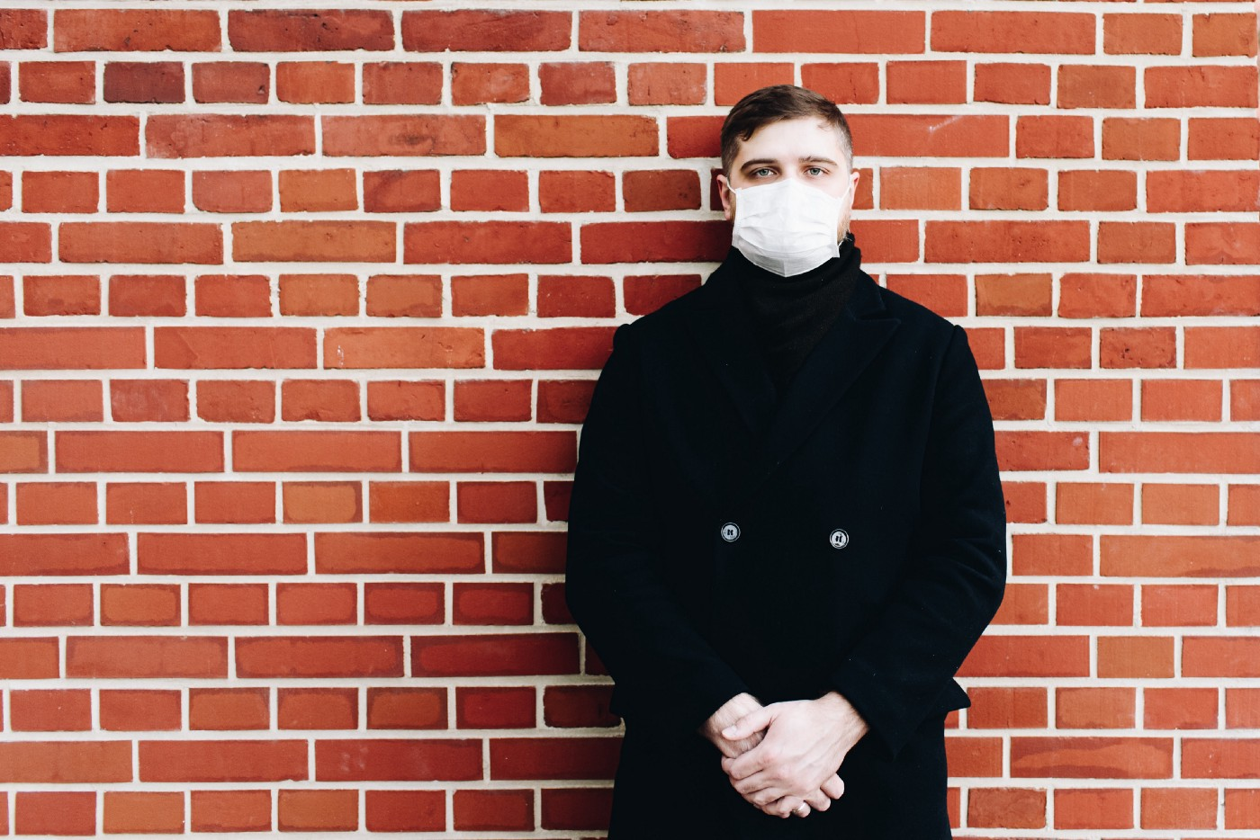 A man in a surgical mask stands against a brick wall.