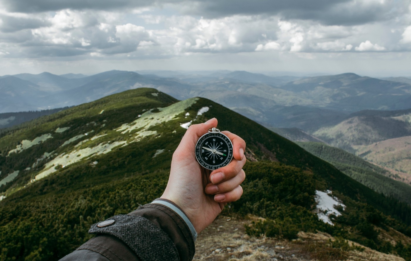 A hand holding a compass with a mountainscape backdrop
