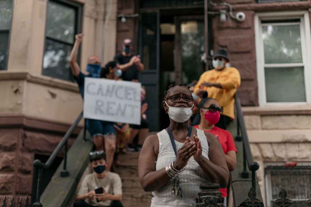 """A group of housing activists in Brooklyn with a """"cancel rent"""" sign. A Black woman stands in the front wearing a mask."""
