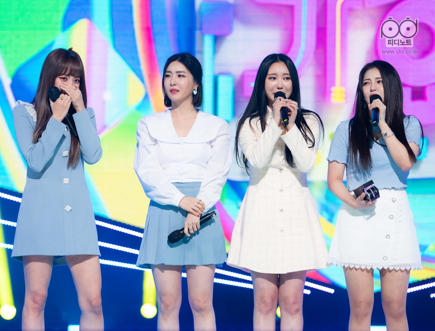 The four members of Brave Girls standing on stage holding mics and crying. One of them is holding a trophy.