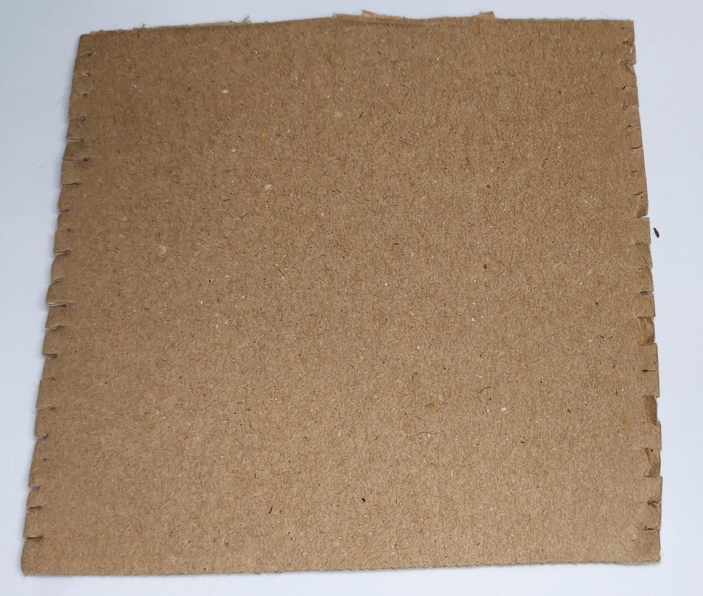 """A square of cardboard with shallow slits cut every 1/4"""" on opposite edges to create a simple cardboard loom"""