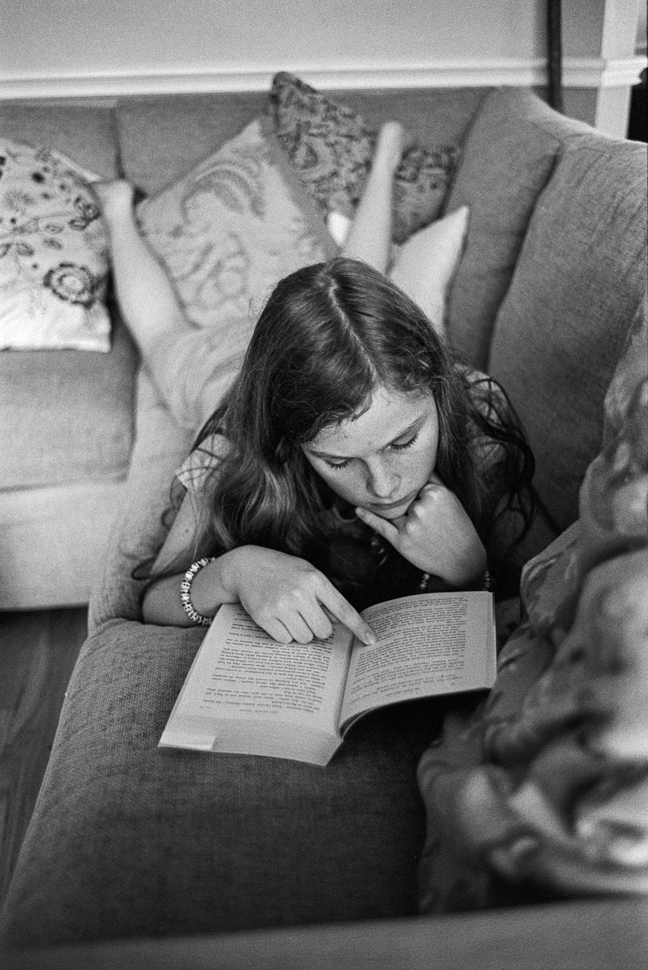 An adolescent girl reading, propped up on her elbows, on a sofa. Her finger absently points at a page