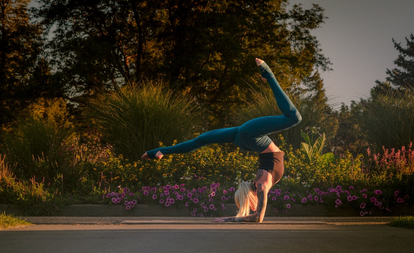 Woman balancing in a yoga pose with flowers in the background