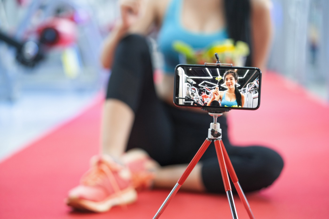 A photo of a woman recording herself doing a workout using her smartphone on a tripod.