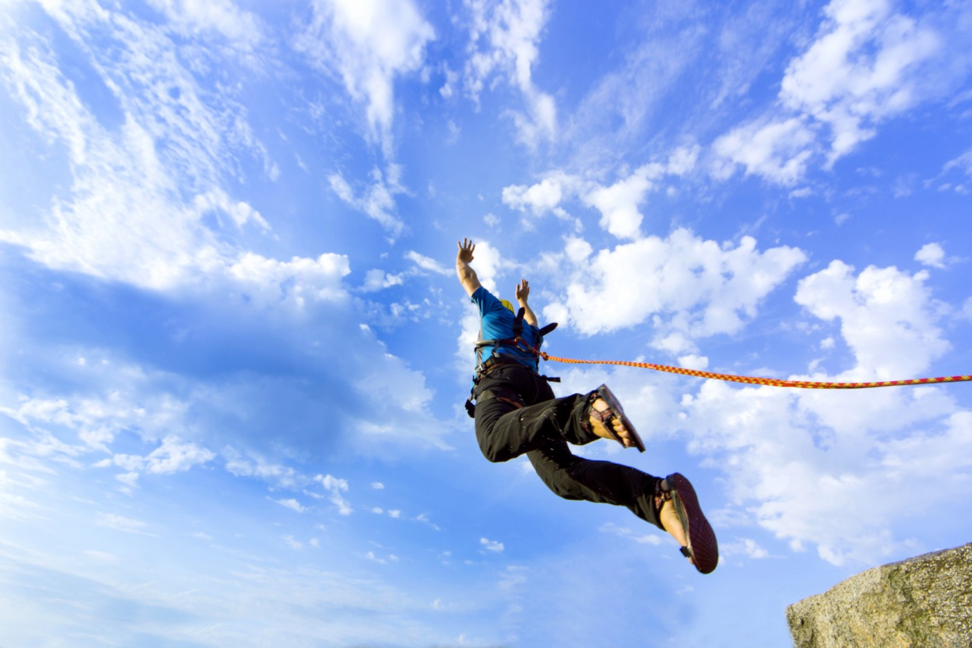 A view of the blue sky as a man bungee jumps.