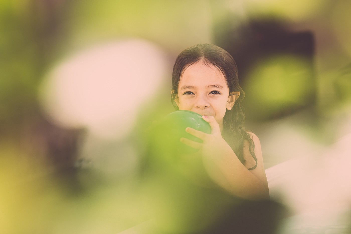 Little girl holding a green balloon with a blurry green background.