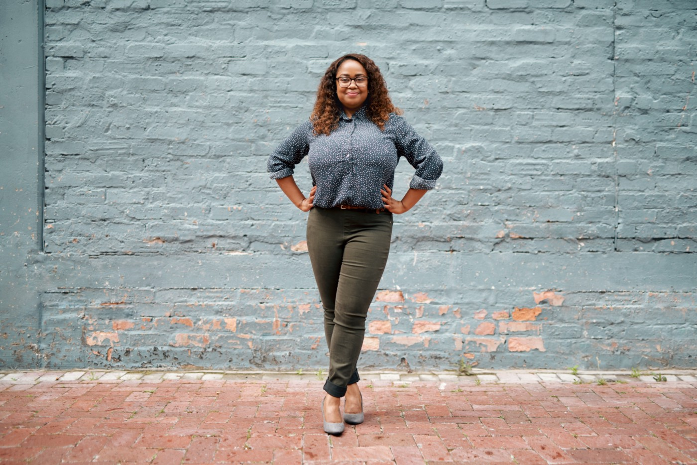 A photo of a confident black woman standing against a blue brick background in a power pose.