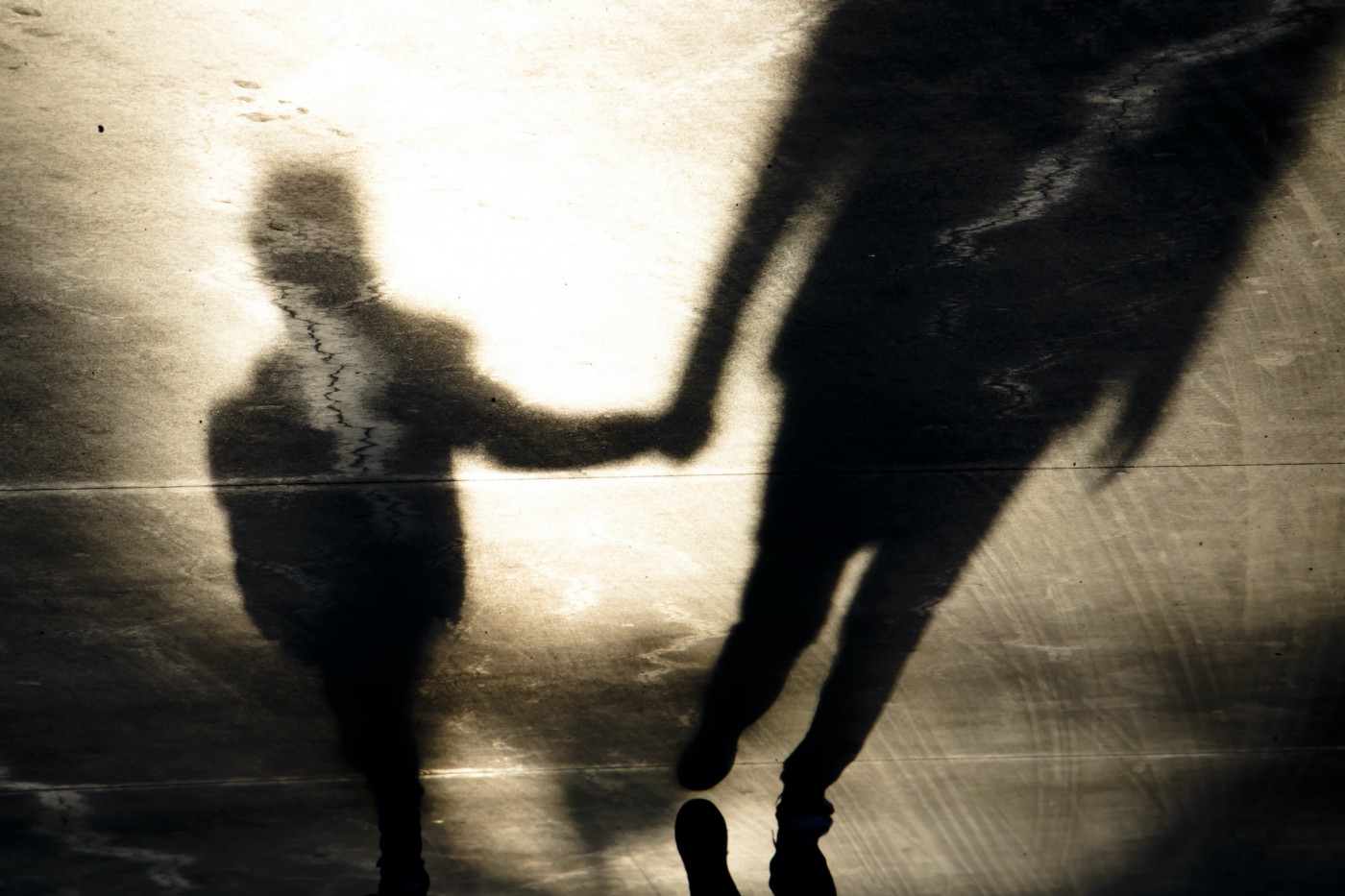 Shadows on pavement cast by a child and an adult holding hands as they walk.