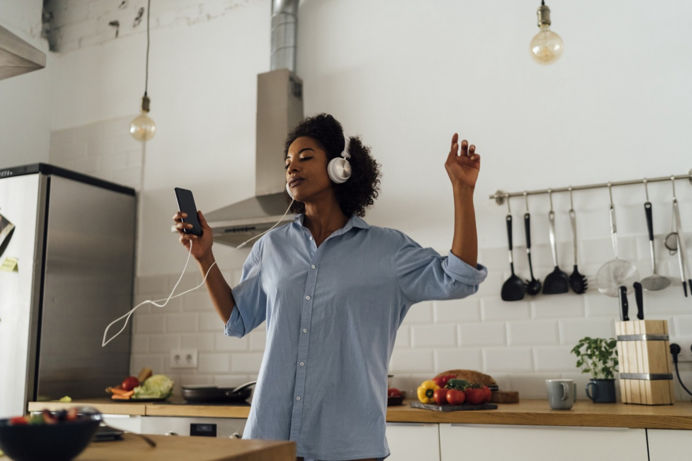 A photo of a black woman listening to music on headphones in her kitchen. She is feeling herself.