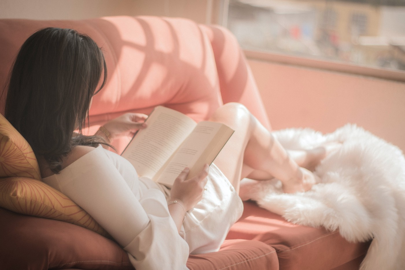 Woman with straight, dark brown hair in a white dress sitting on pink couch reading a book. Her feet are tucked into a white fluffy blanket and she is relaxed.