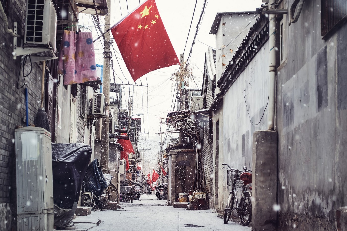 A Chinese flag overhanding and urban street with snow falling.