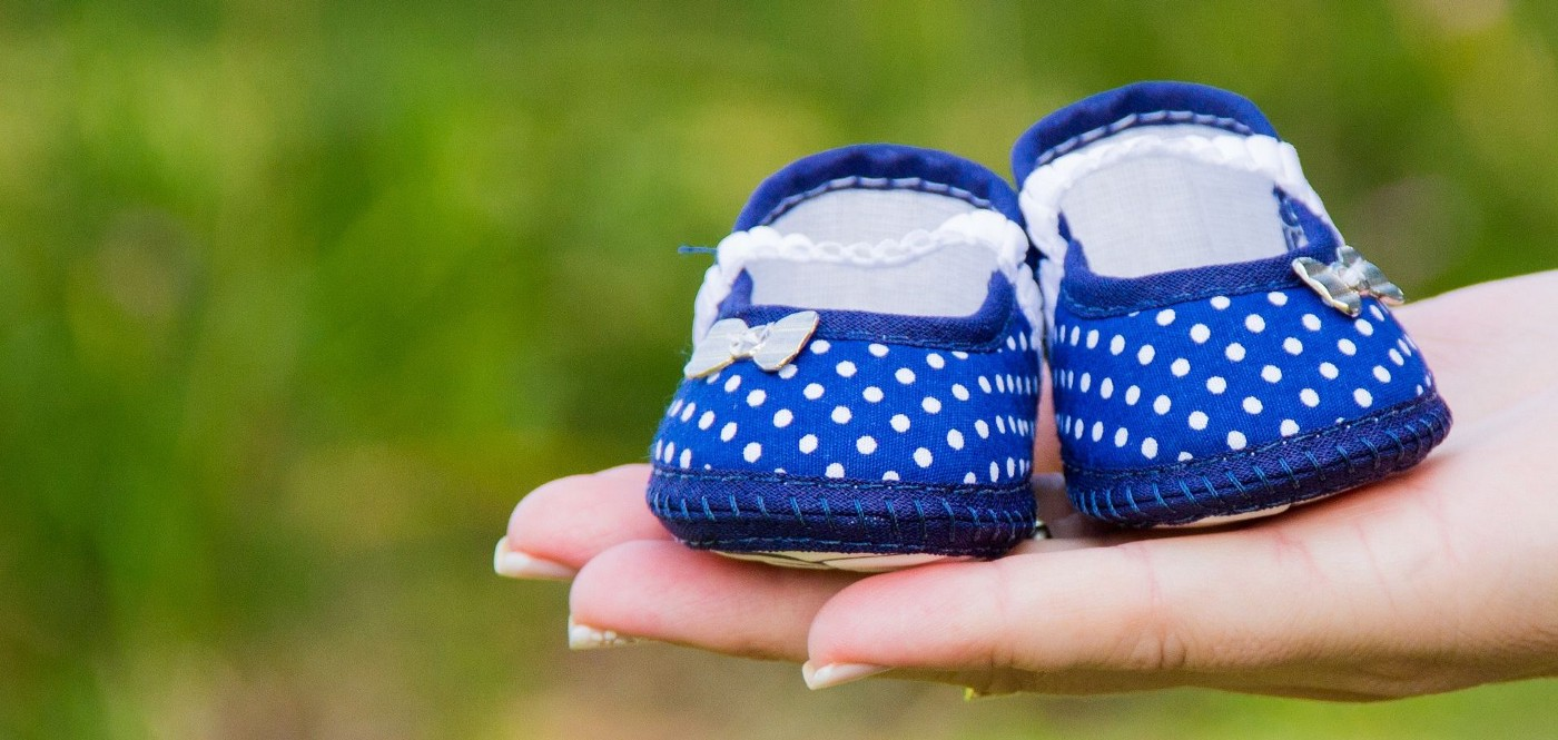 A pair of dark blue polka dot baby shoes balanced on the palm of a woman,