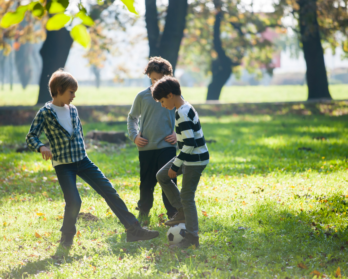Three boys playing with a football outdoors.