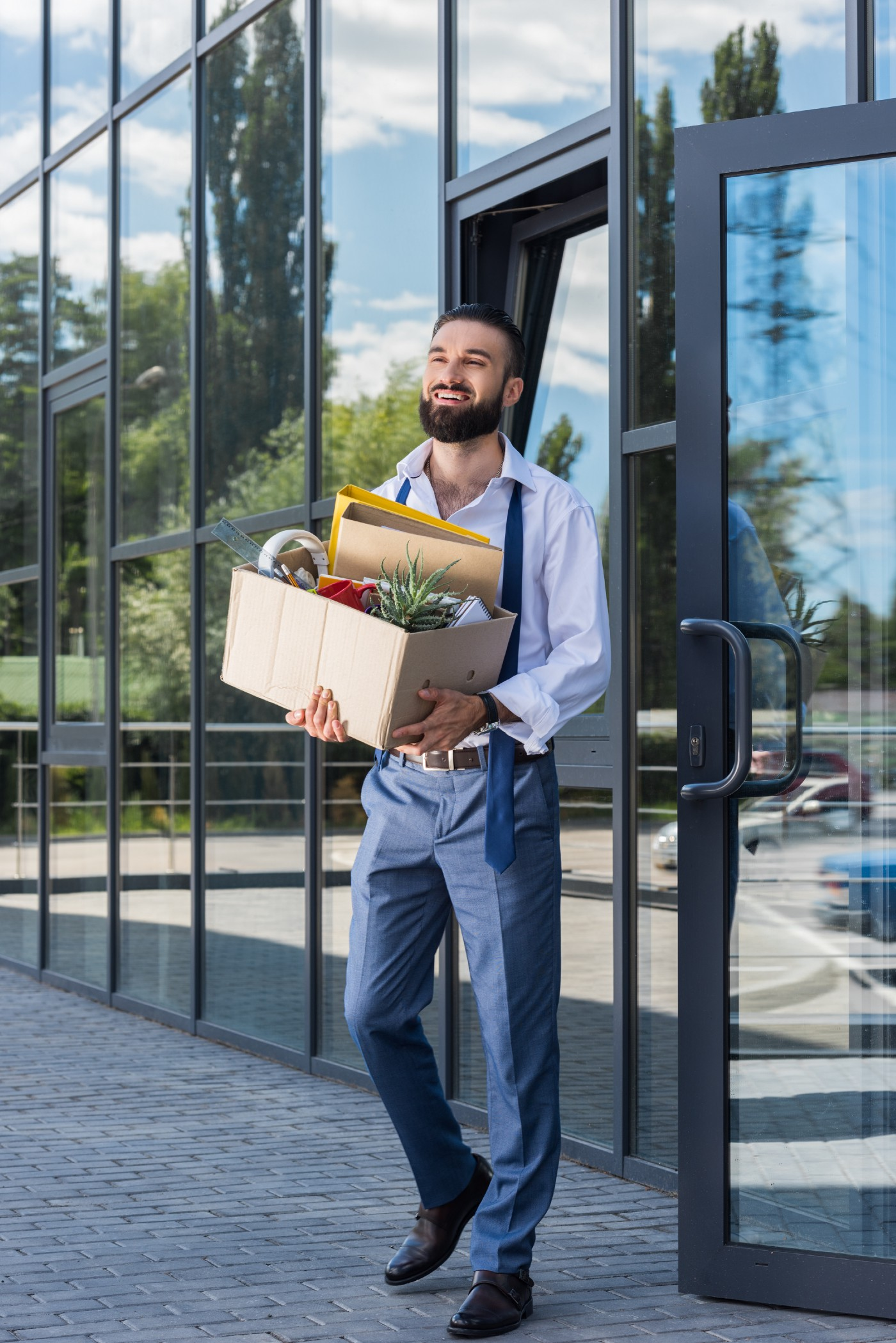 Man leaving work having cleared out his desk. He looks happy about it.