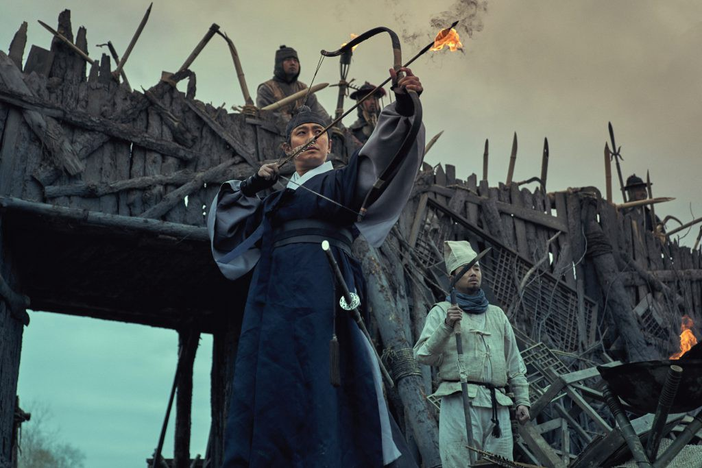 A man in seventeenth century Korean clothing aims a flaming arrow in front of a wooden barricade.