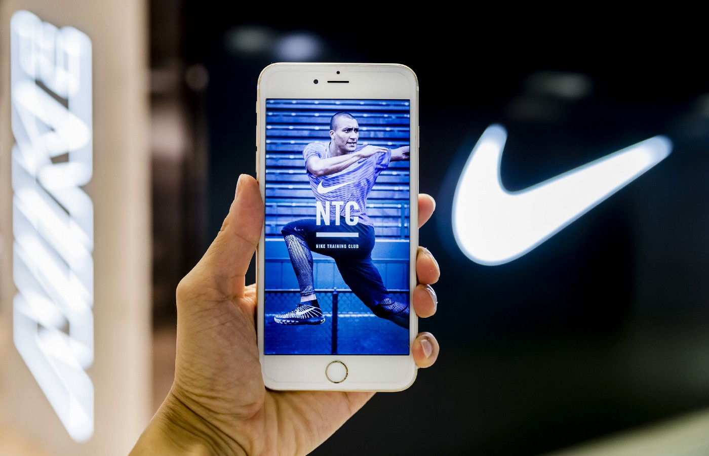 The Nike Training Club (NTC) app screen is displayed on a phone, held up against the Nike swoosh logo.