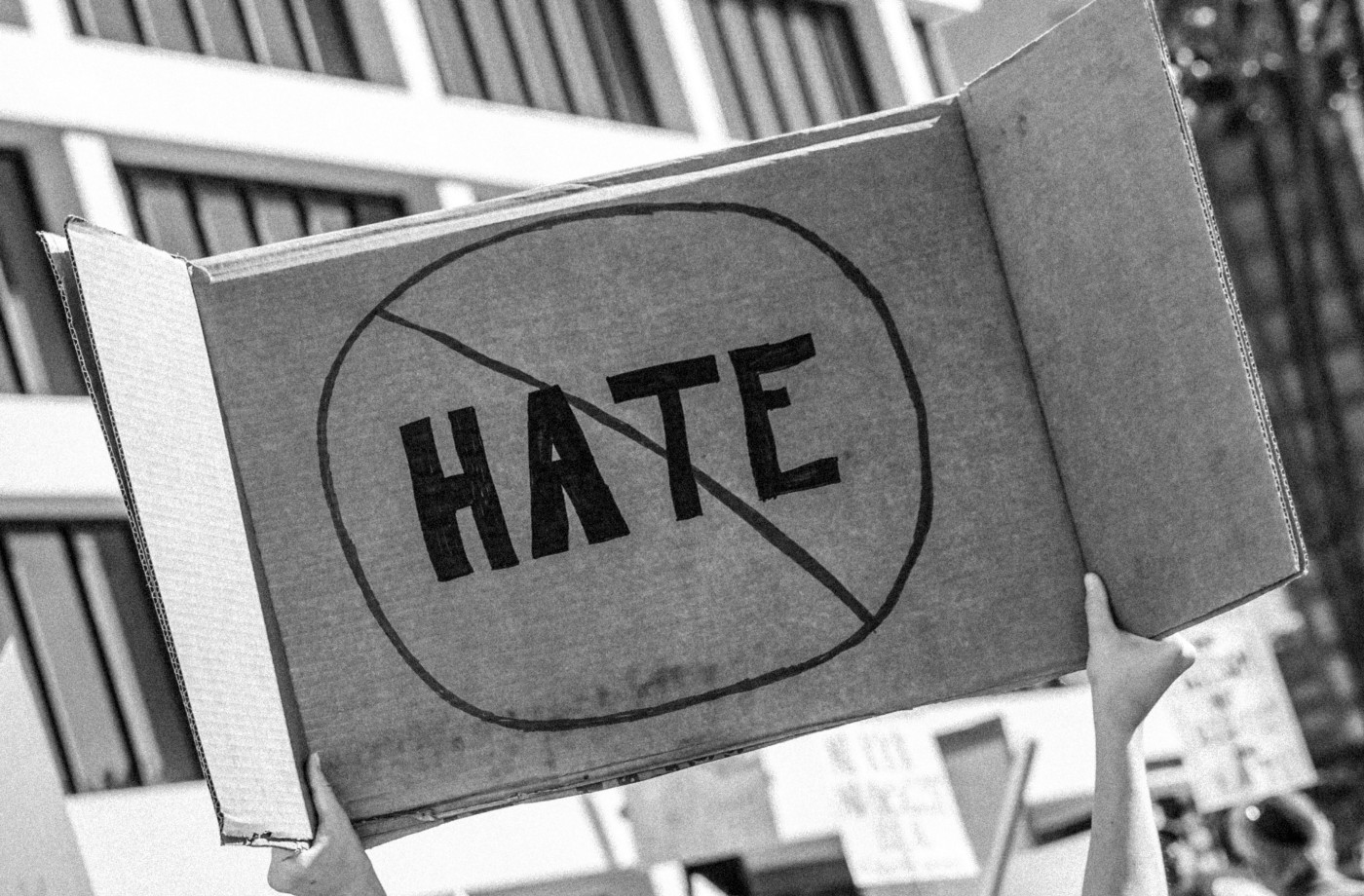 A black and white picture of a hand-written sign at a demonstration. The sign has the word HATE on, crossed out.