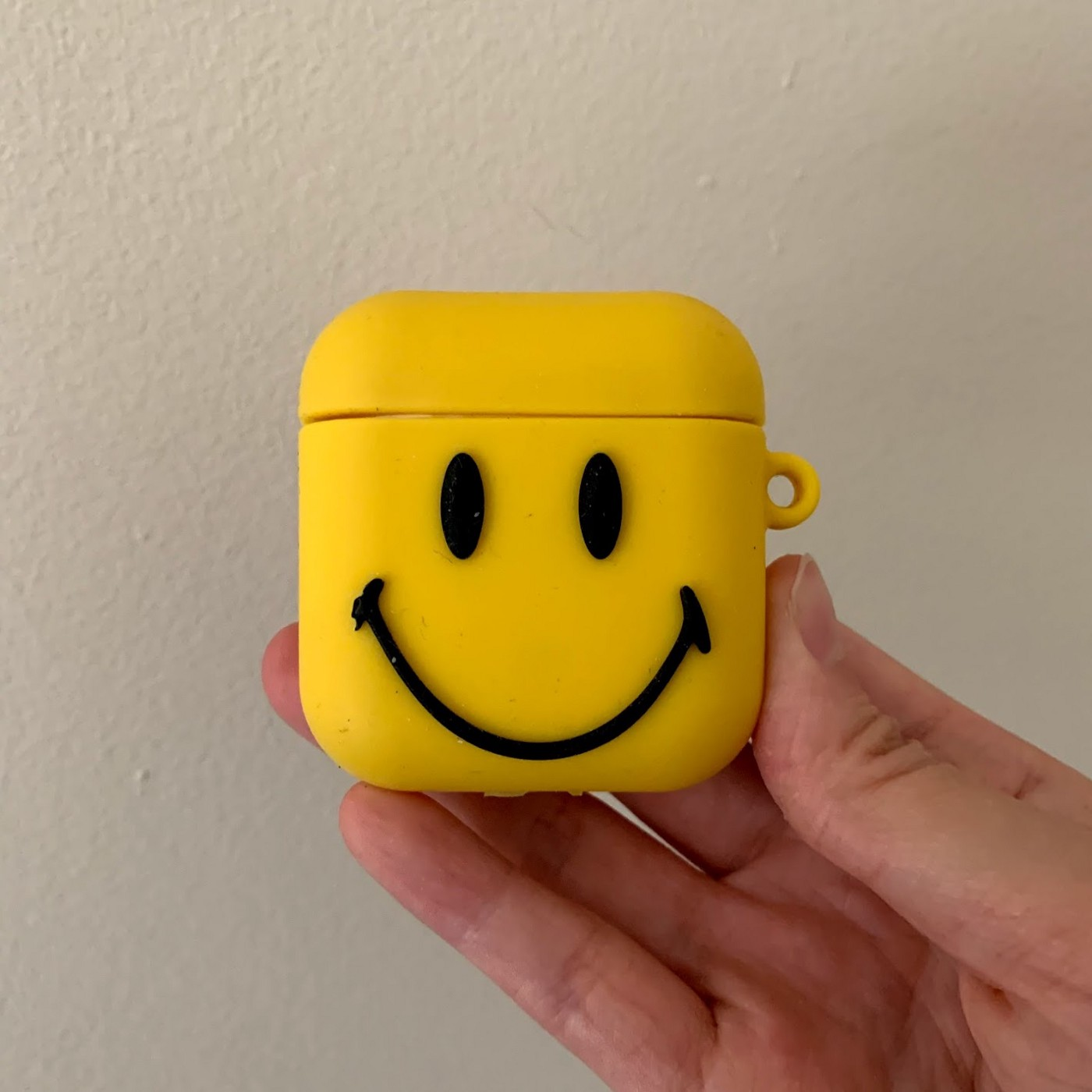 Bright yellow square AirPods case with smiley face decal