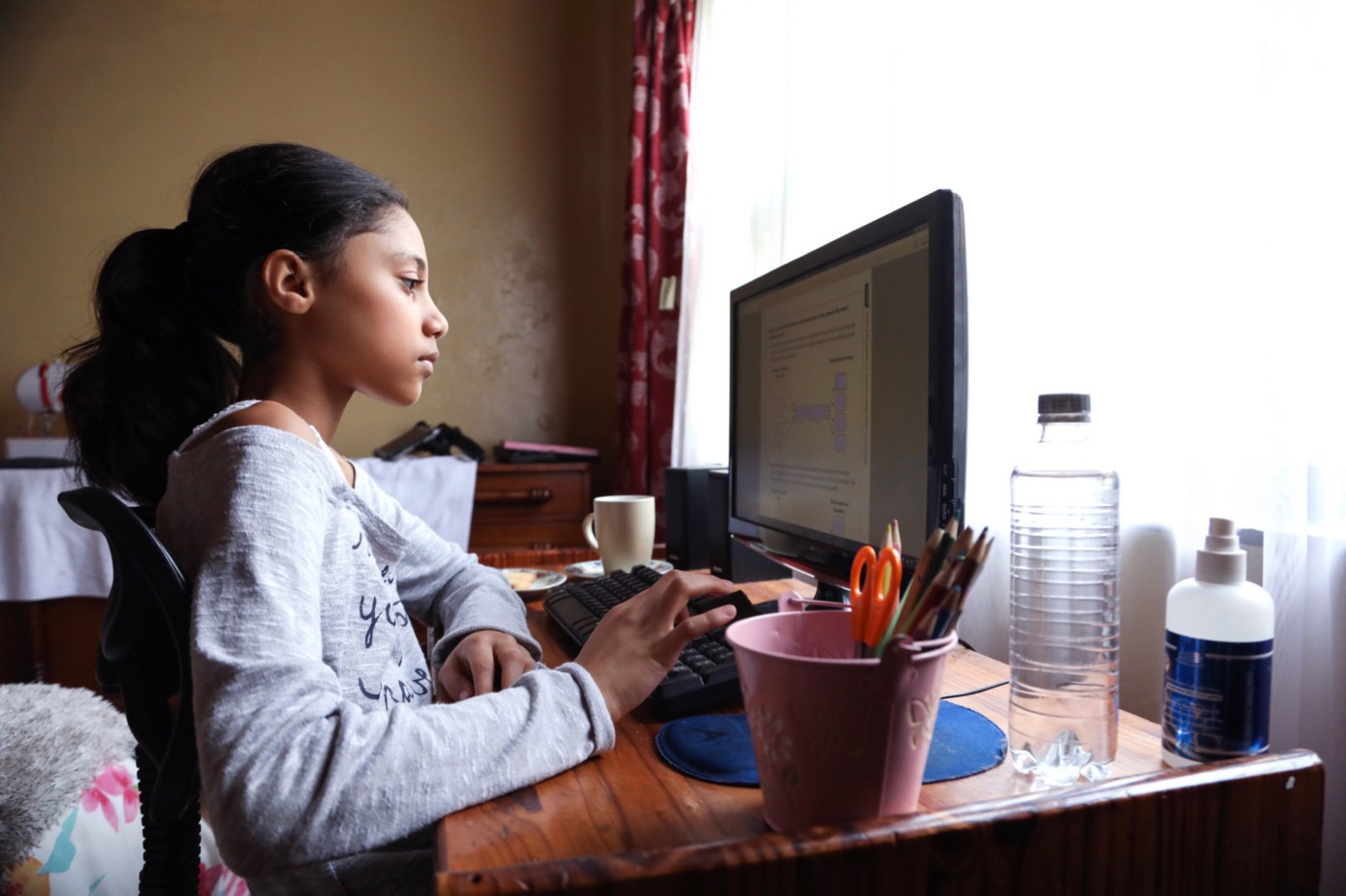 A photo of a young South Asian girl doing homework on her computer at her desk.