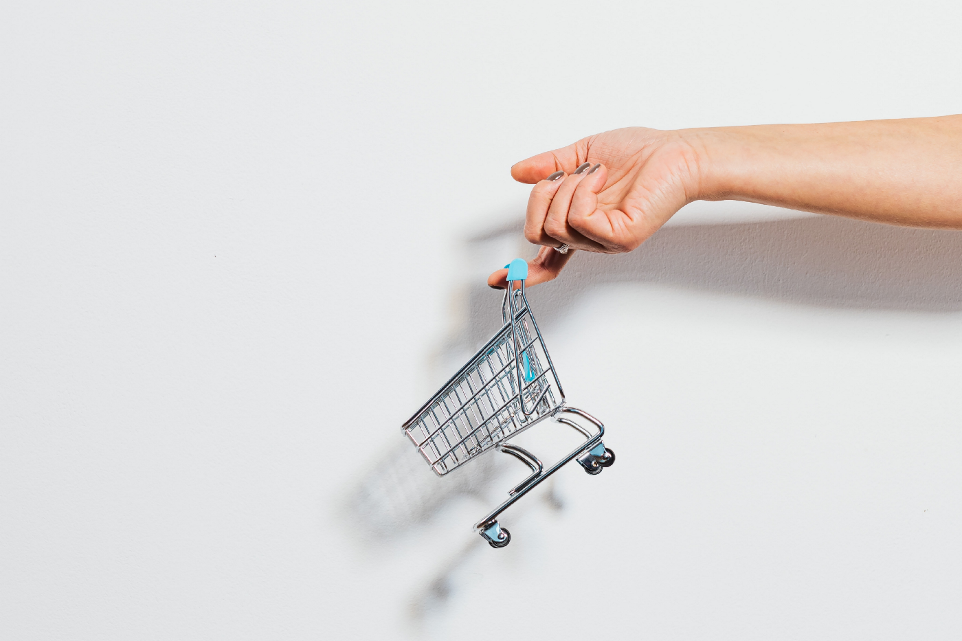 A mini shopping cart dangles off a person's finger.