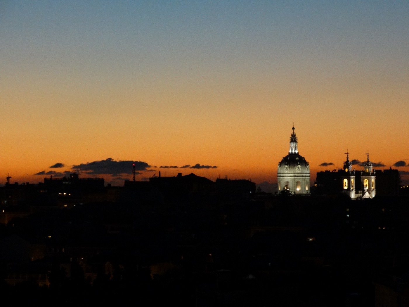 A cathedral dome illuminated on the dark skyline at sunset.