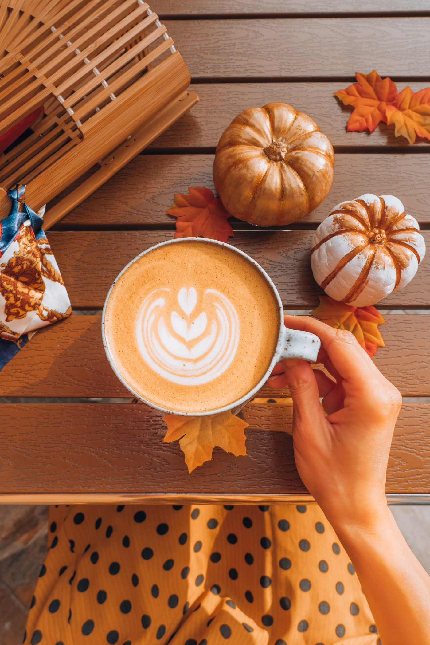 A pumpkin spice latte surrounded by orange leaves and mini pumpkins