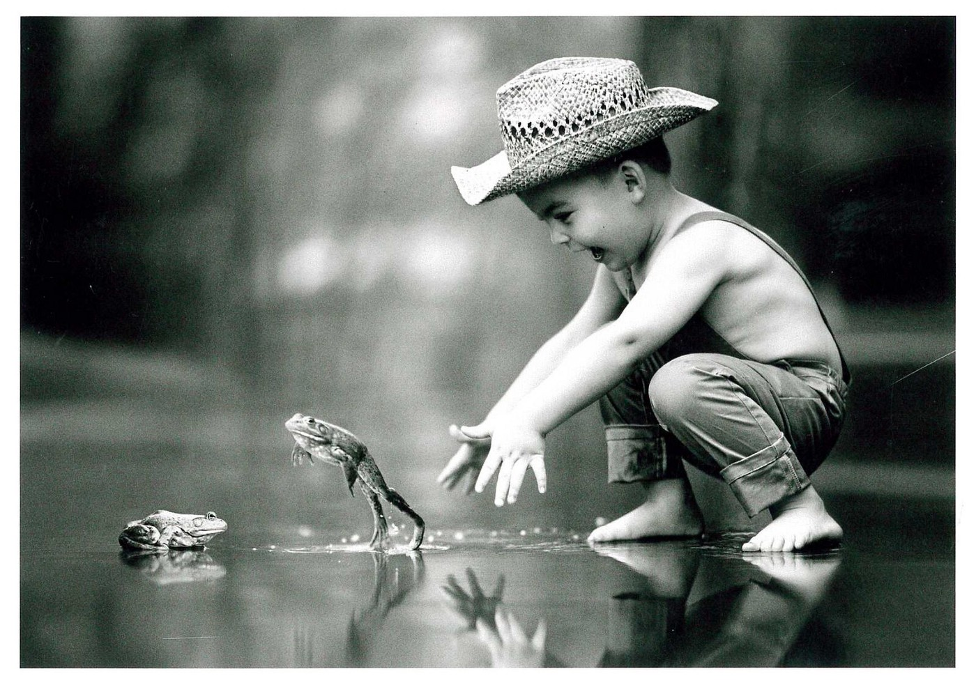 Black and white photo of a barefoot boy in overalls and a straw hat reaching for a jumping frog.