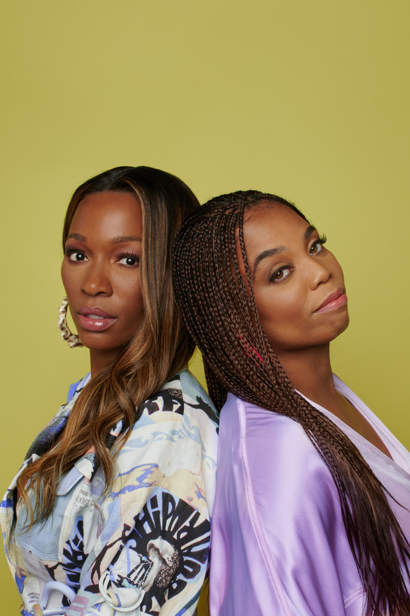 Closeup portrait photo of Jemele Hill and Cari Champion standing back-to-back.