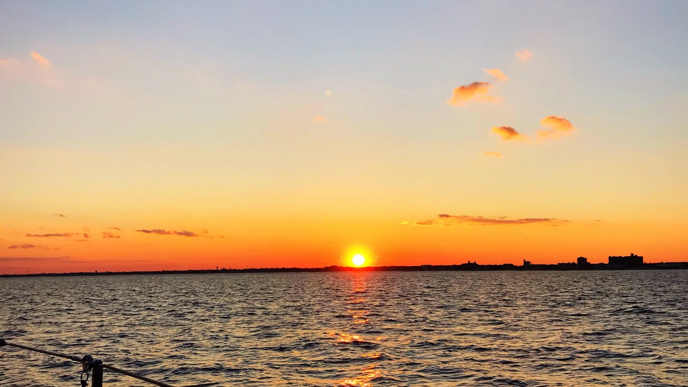 A sunset off the coast of New Jersey from the water.