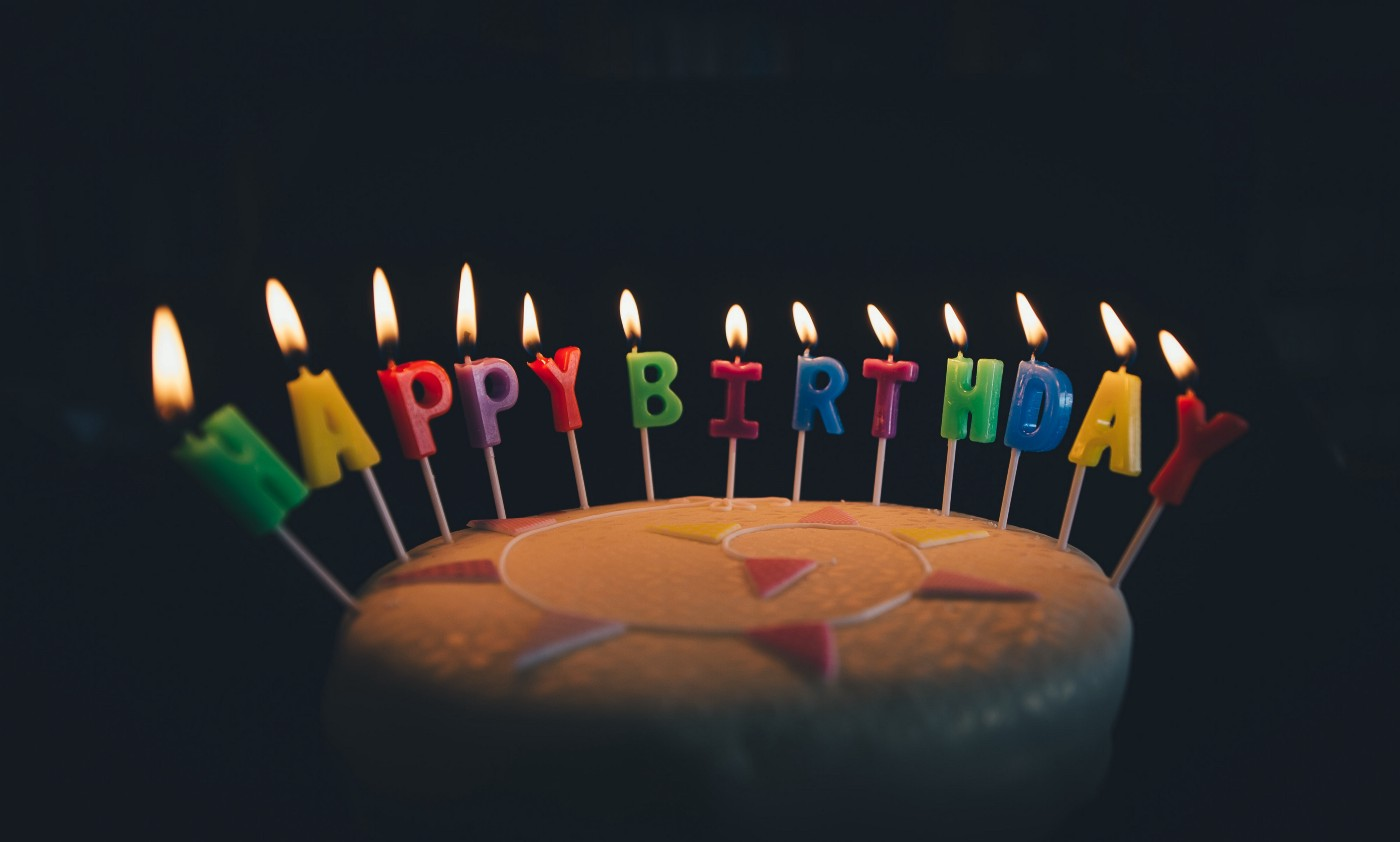 """A chocolate cake with lit candles spelling """"Happy Birthday."""""""