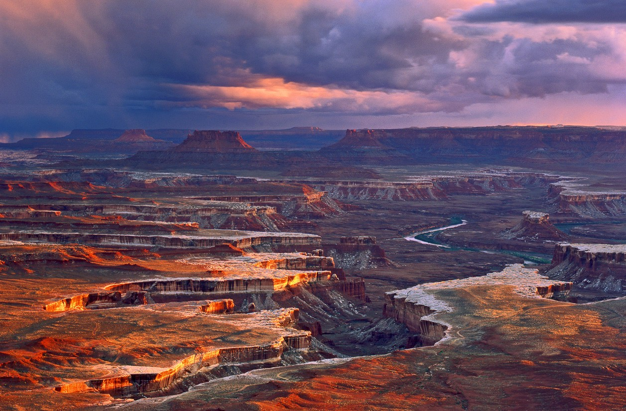 The Maze landmark in Canyonlands National Park. The image is of vast canyons that were once formed by rivers and water. It is beautiful, warm, full of colors, with a pink sunset.