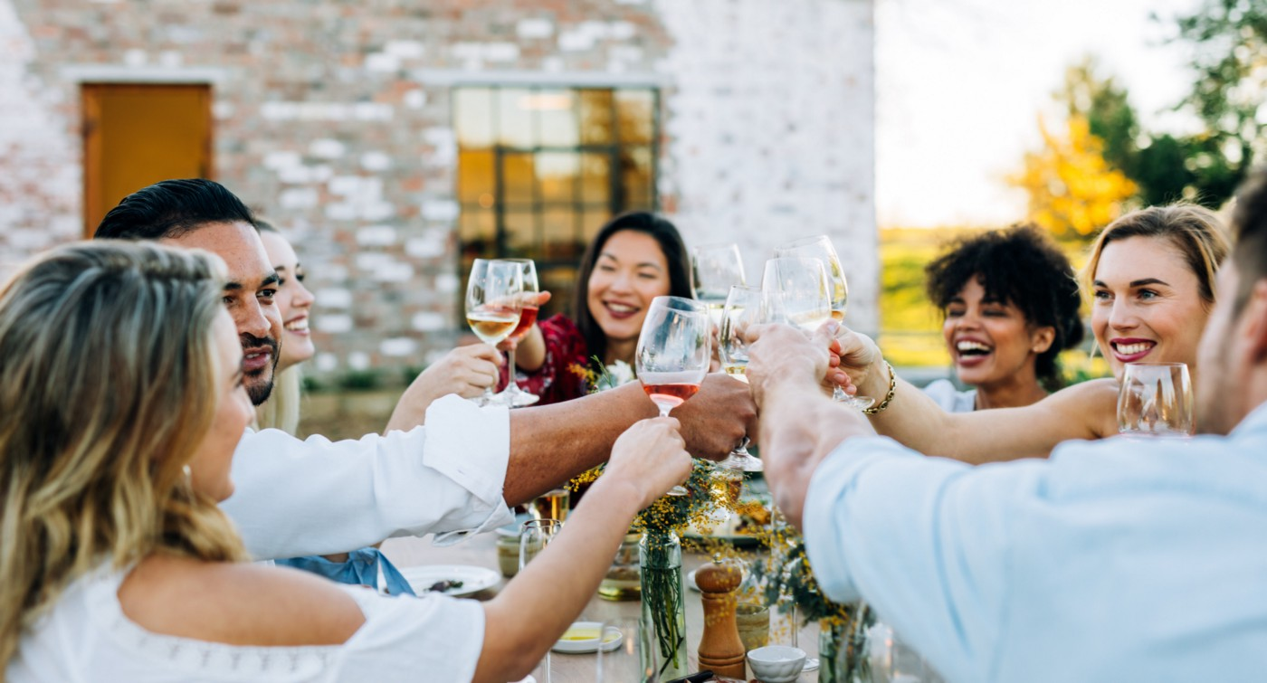 Friends dining outside and enjoying wine.