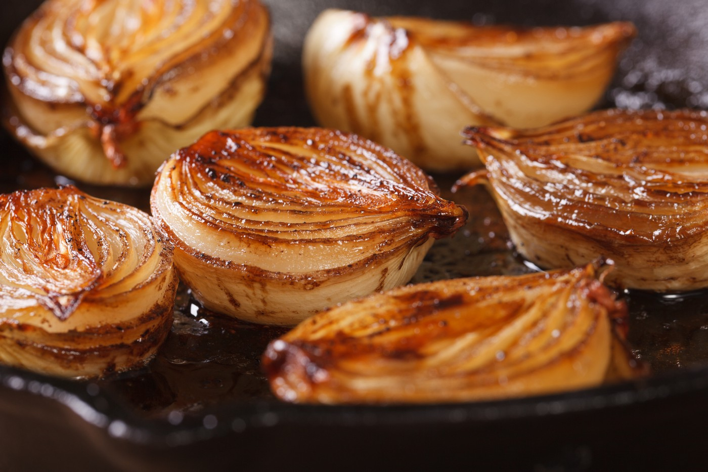 Roasted onions halved and facing upwards in a cast iron pan.